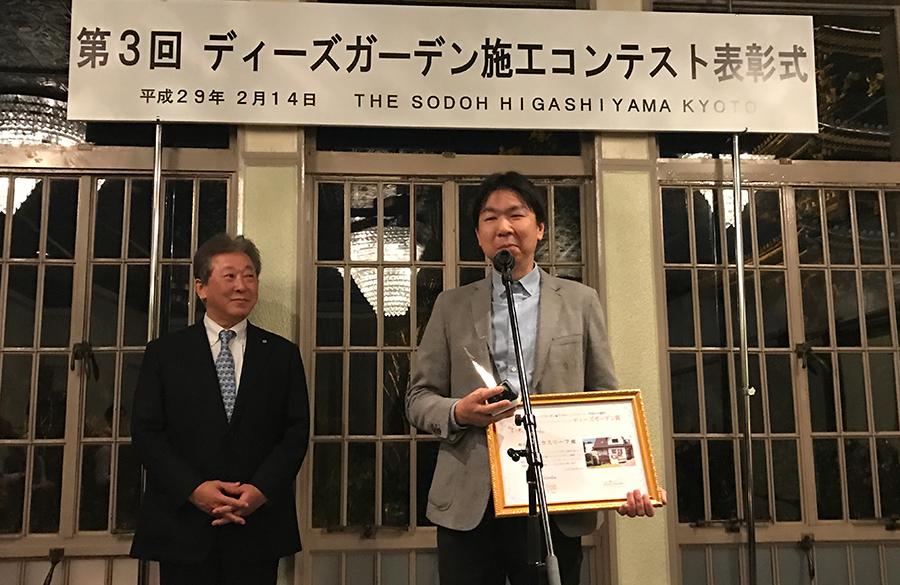 橋本社長の横で緊張気味にスピーチする富山です。